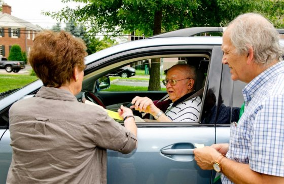 Assistant Registrar Joan Caldwell, left, and Moderator John Vecchiolla, right, help Joe Mayone, center, vote from his vehicle during the Republican Primary on Tuesday, August 12, 2014. Curbside voting is a service available to anyone who has difficulty getting into the polling locations.